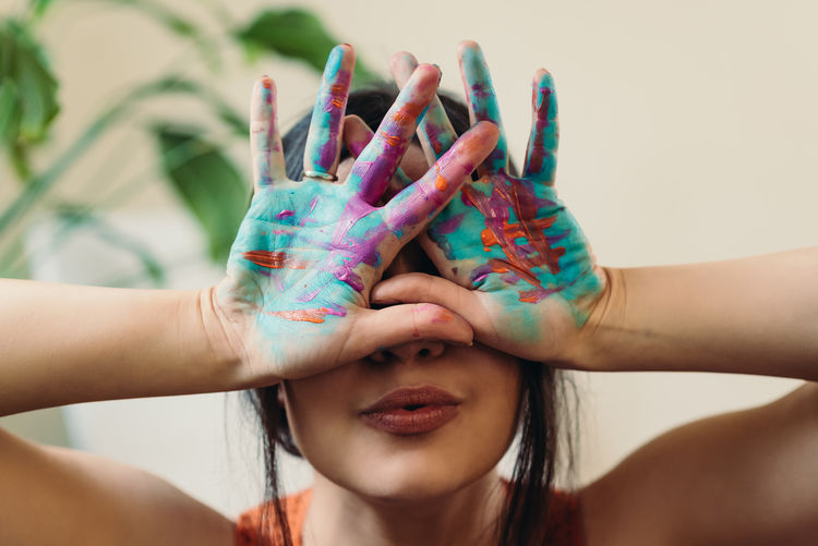 Woman with hands painted covering face