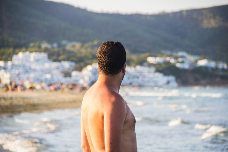 Side view of shirtless man standing at beach during sunset