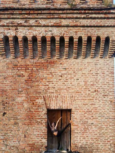 Ballerina performing at doorway of historic building