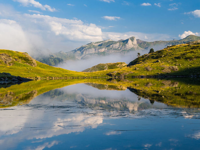 Lake and mountains against cloudy sky at pyrenees