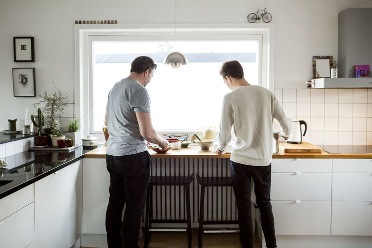 Rear view of friends standing in kitchen at home