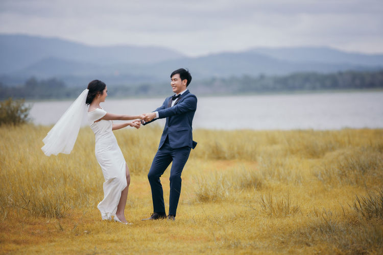 Full length of newlywed couple holding hands outdoors