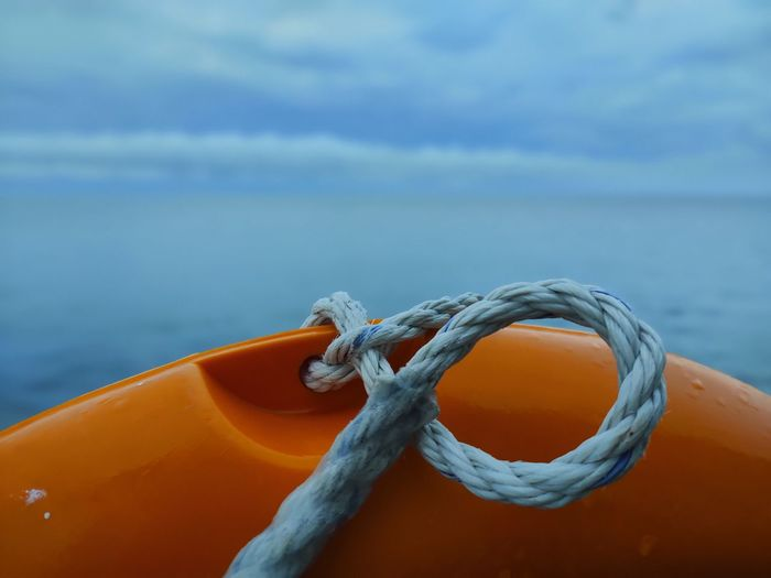 Close-up of rope tied on sea against sky