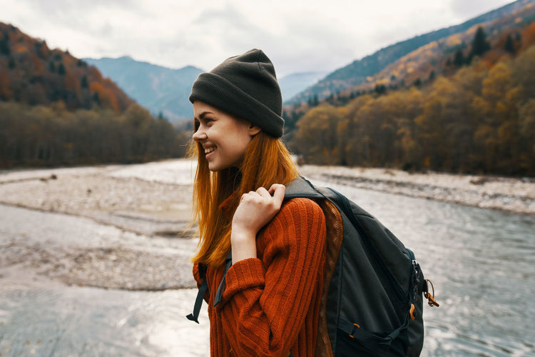 Portrait of smiling young woman in hat standing outdoors