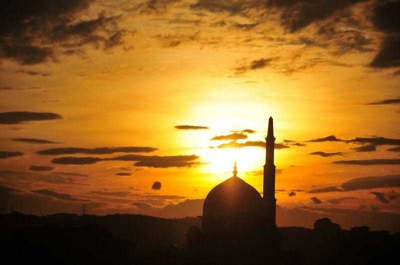 Silhouette mosque against orange sky