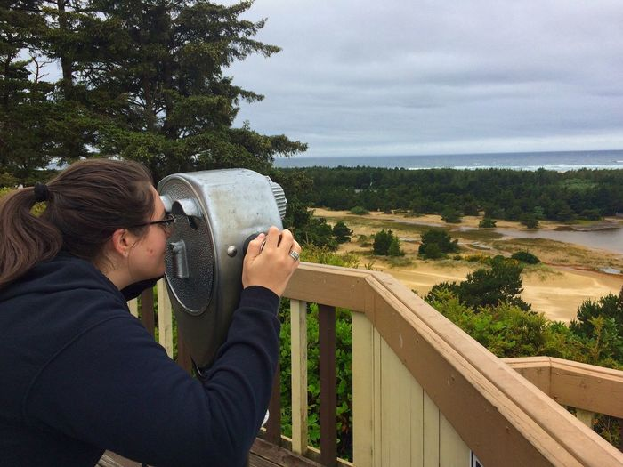 Side view of young woman looking through coin-operated binoculars against sky