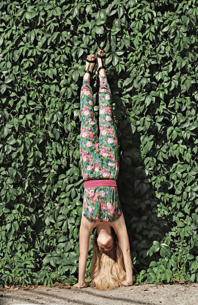 Young Blonde Woman Making A Handstand, Standing Upside Down, Green Leaves Background, Woman Cameleon In Green Jumpsuit With Pink Floral Pattern All Over It All Green Blonde Blonde Girl Cameleon Floral Pattern Freedom Co Green Color Green Leaves Green Nature Hand Stand  Handstand  Handstandseverywhere Jumpsuit Sun Light Sunset Up Side Down Upside Down Upside Down Photography Upsidedown Upsidedown Having Fun! Vertical Woman Portrait Young Young And Free Youth Of Today