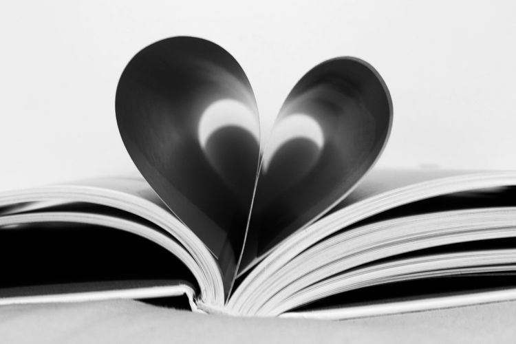 Close-up of heart shape on book against white background