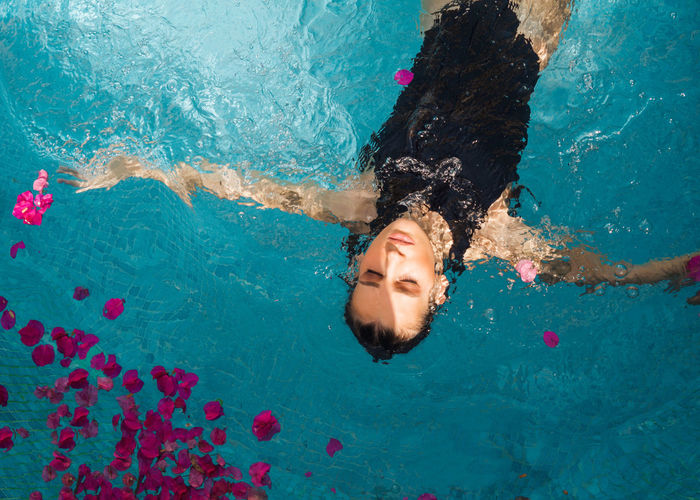 High angle view of woman swimming in pool full of flowers