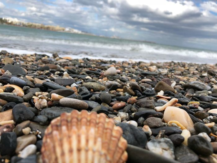Close-up of pebbles on beach against cloudy sky