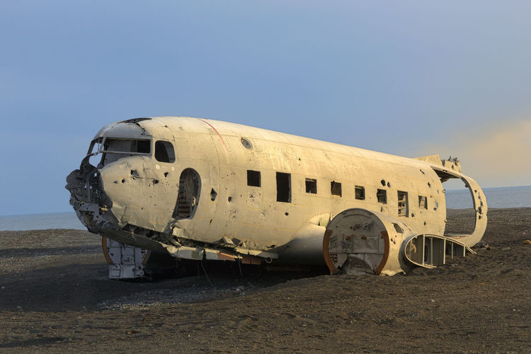 Abandoned airplane on sand against sky