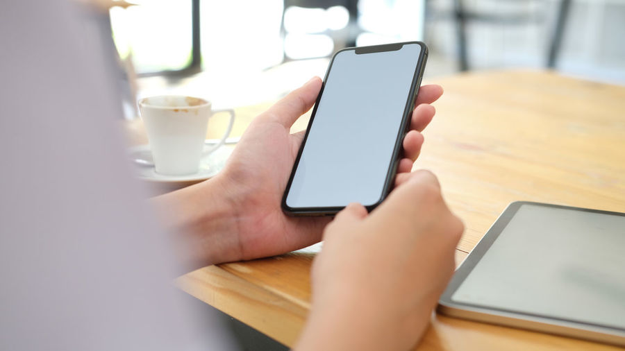 Midsection of person holding mobile phone on table