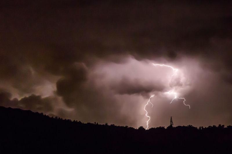 Lightning over silhouette trees against dramatic sky