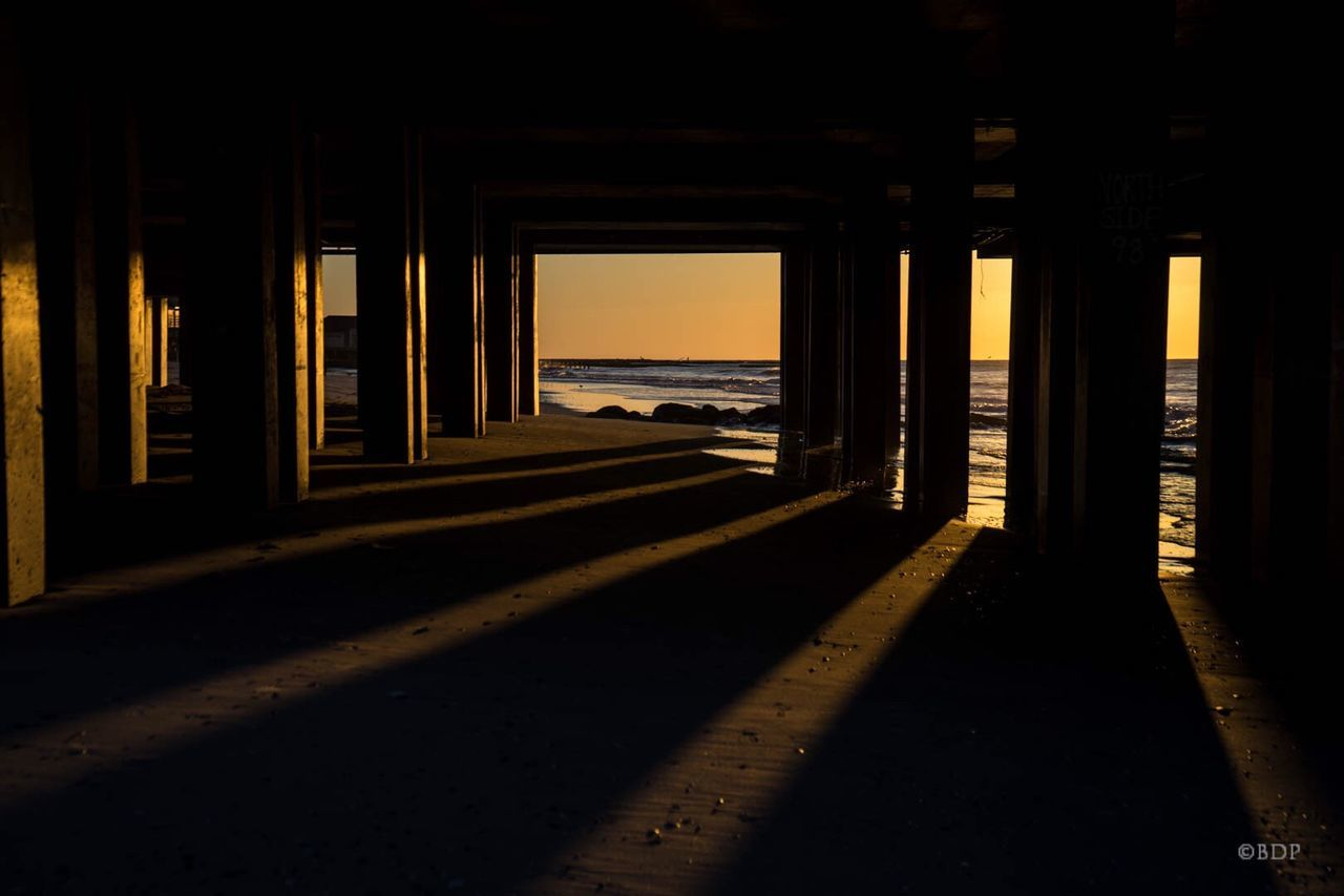architecture, sunlight, built structure, sea, underneath, water, indoors, architectural column, silhouette, shadow, sunset, no people, day, nature, under, horizon over water
