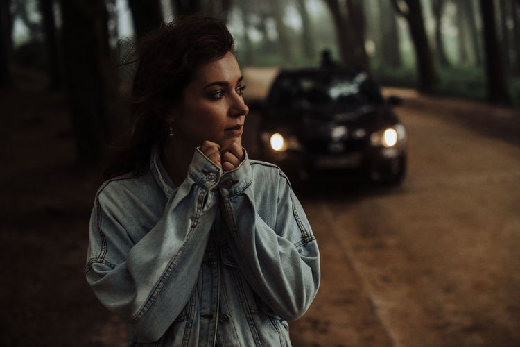 Portrait of young woman standing in car