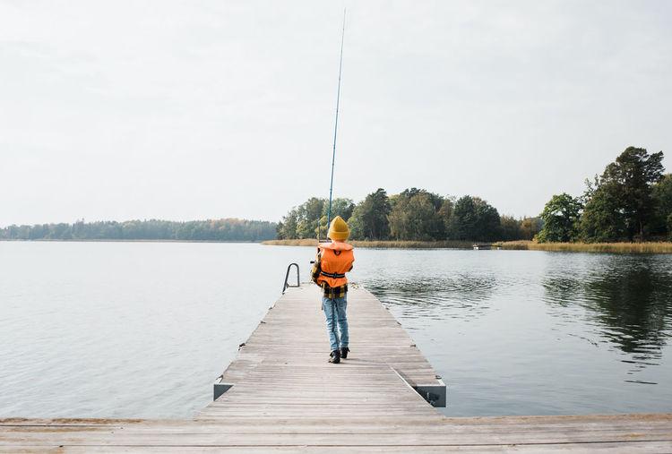 Man fishing on pier over lake against sky