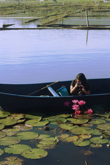 Woman Photographing Water Lilies From Boat