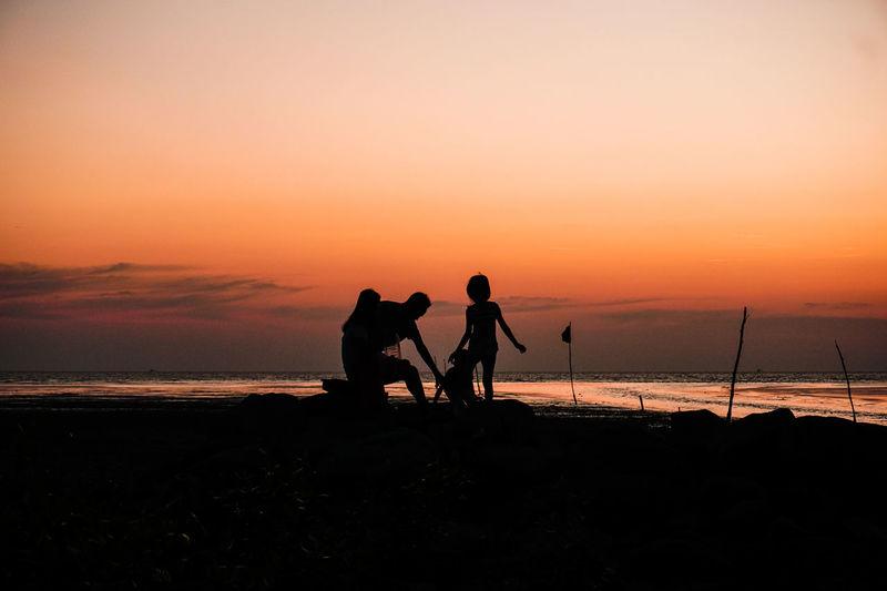 Silhouette family at beach against orange sky