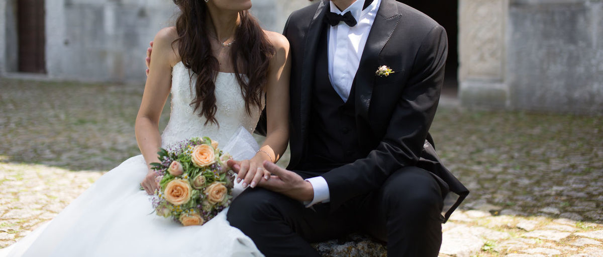 Midsection of bride and groom sitting on rock