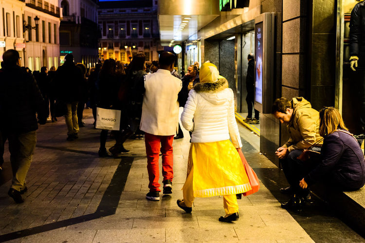 A women wearing a colourful Indian ethnic style yellow dress and trousers leaving a shop in Preciados during late evening in Madrid. Business City City Centre Citylife Clothes Depth Of Field Editorial  Editorial Fashion Ethnicwear Evening Fashion Holding Leisure Activity Madrid Men People Preciados Real People Shopping Street Street Fashion Streetphotography Walking Woman Yellow