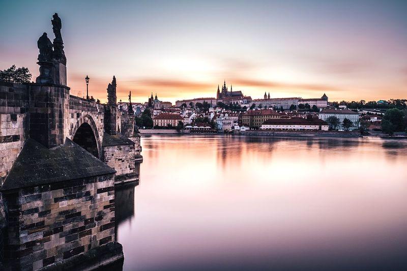 Charles bridge over vltava river in city during sunset