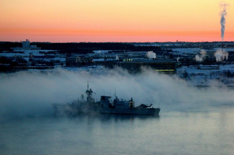 Navy frigate leaving harbor at dawn