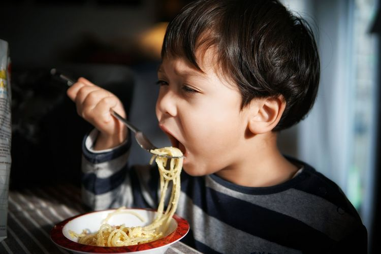 Close-Up Of Boy Eating Pasta In Bowl At Table