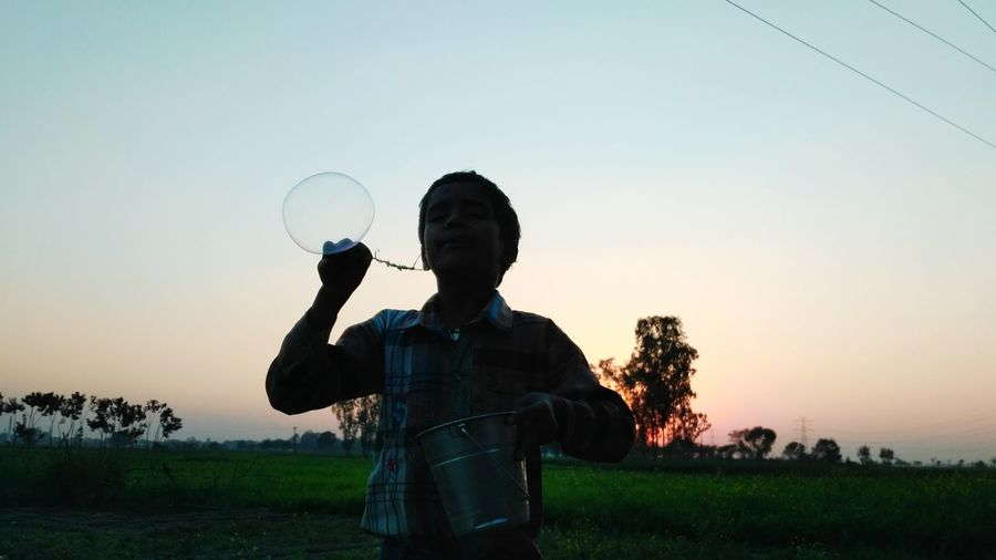 Boy with bucket blowing bubble on field during sunset