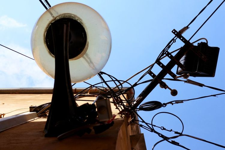 Directly below shot of street light and electric cables on building against clear sky