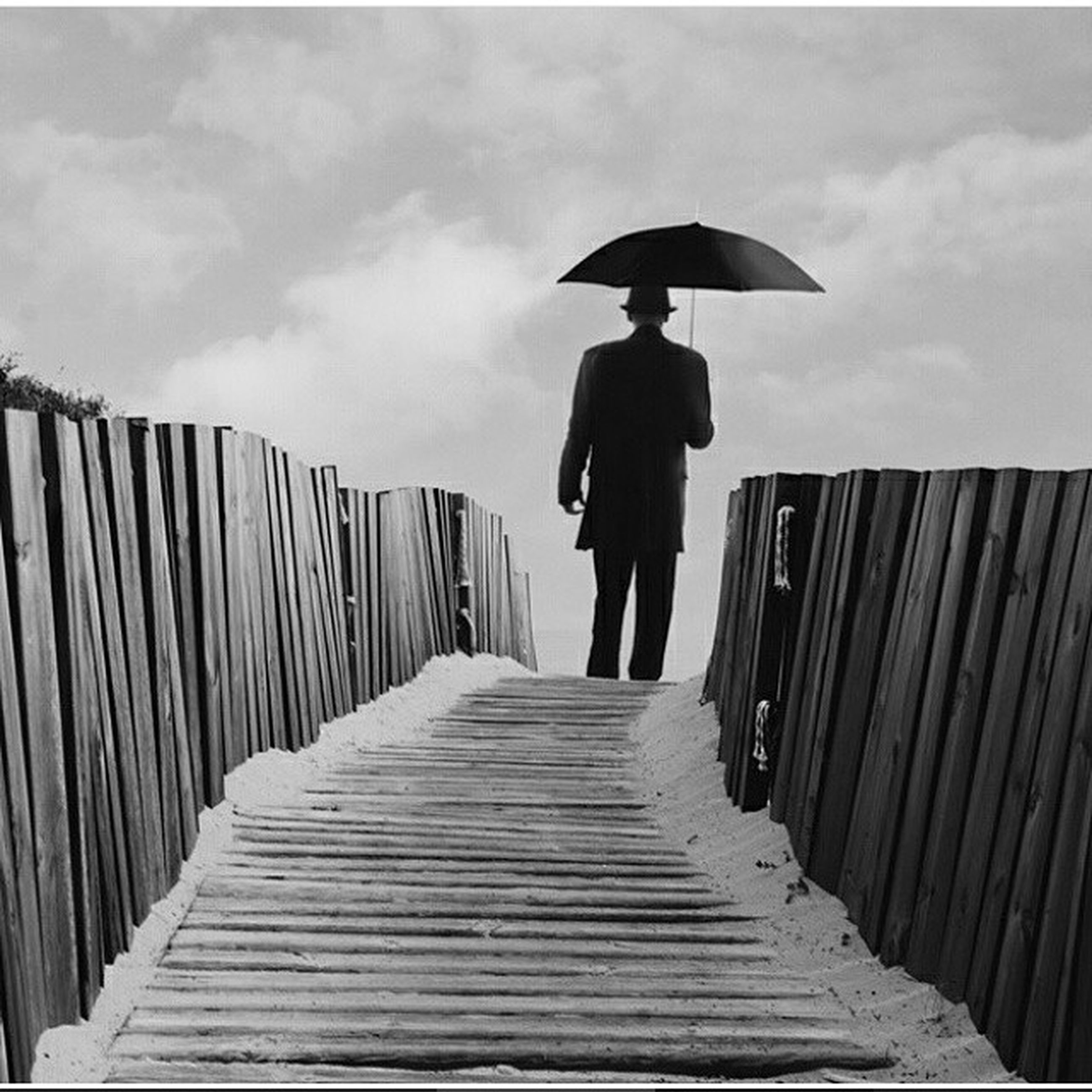 rear view, full length, the way forward, sky, walking, lifestyles, men, leisure activity, railing, boardwalk, diminishing perspective, cloud - sky, standing, cloud, person, built structure, wood - material