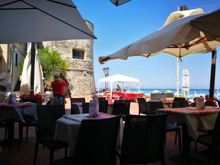 Laigueglia, Chair Table Restaurant Cafe Food And Drink Industry Day Bar - Drink Establishment Outdoors Luxury Hotel Vacations Place Setting Luxury No People Sky Sea Water Food