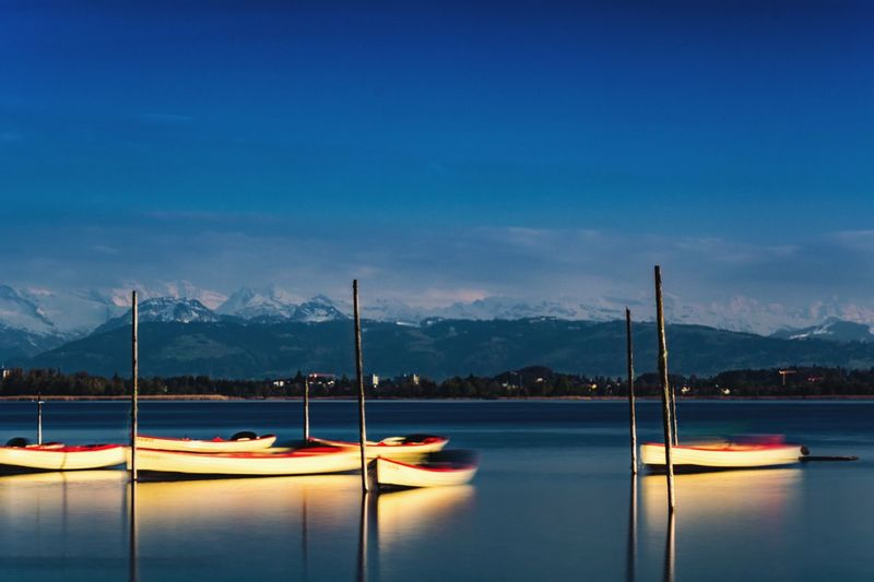 Fishing Boats Anchored On River Against Snowcapped Mountains