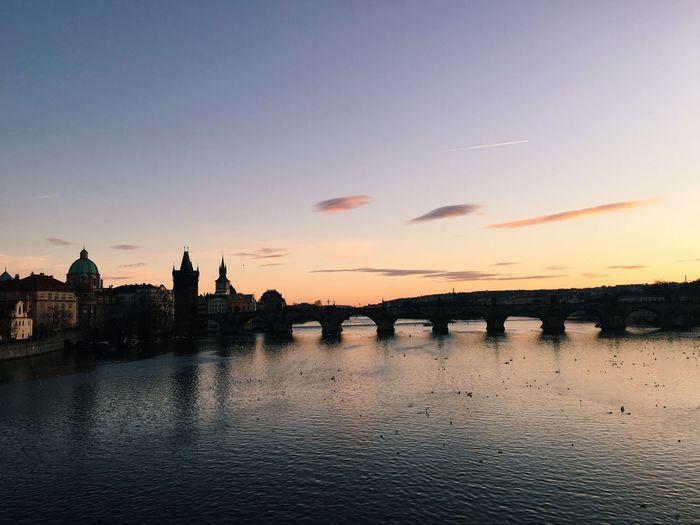 Charles bridge over vltava river against sky during sunset