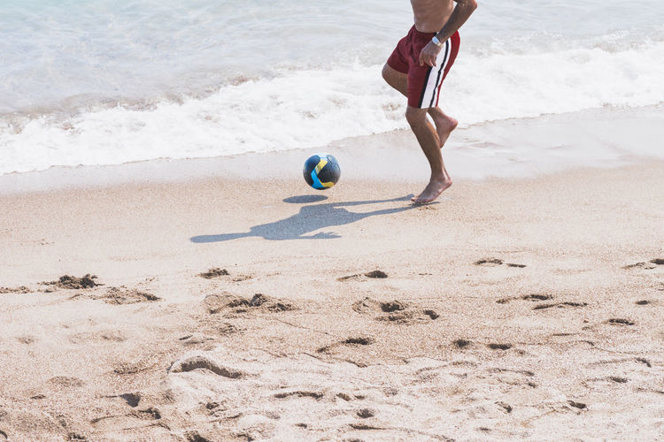 Low section of person playing soccer on beach