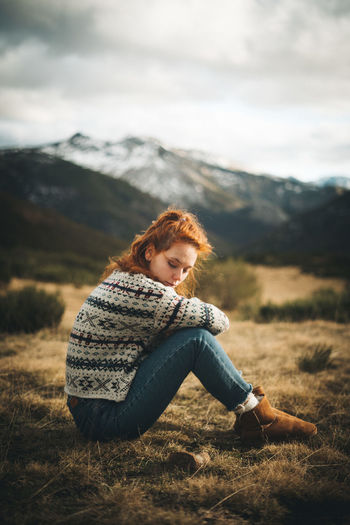Woman sitting on field against mountains