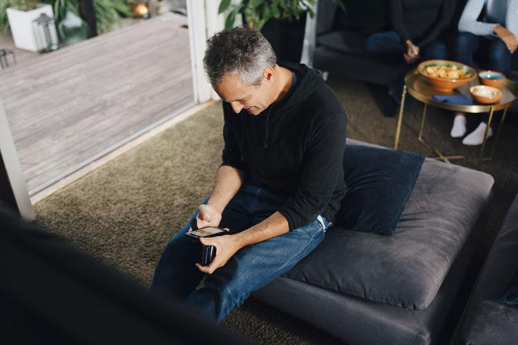 Man looking at camera while sitting on sofa