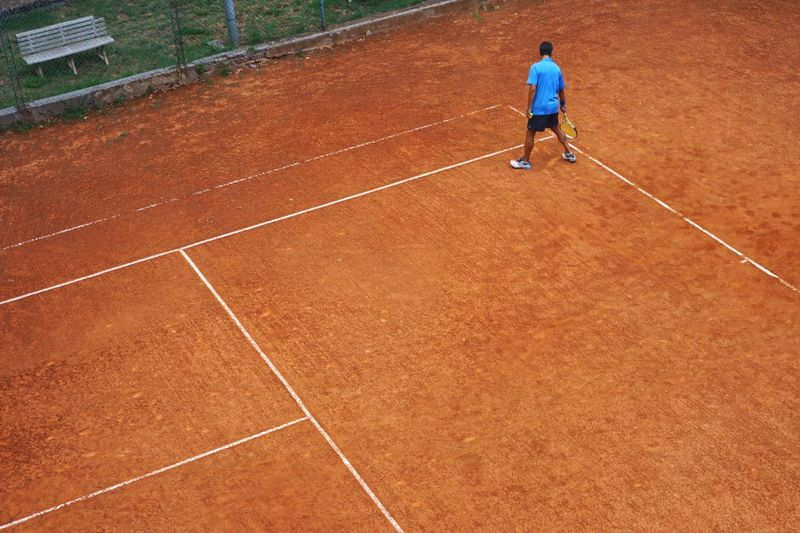 Orange Color Blue Color Clay Courts One Person Sport Full Length Leisure Activity Real People Lifestyles Casual Clothing Day Competition Sports Clothing Tennis Outdoors Brown Court Shorts