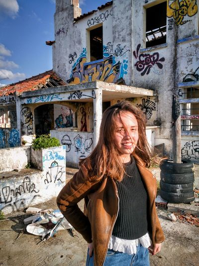 Portrait of smiling woman standing against abandoned building