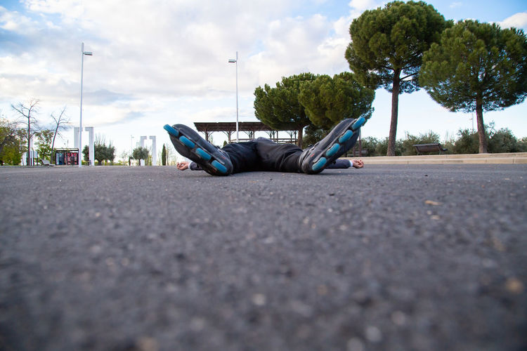 Surface level of man sleeping on road against sky