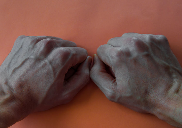 Hands of a young boy with marked veins isolated on orange background. Man Orange Adult Aggression  Body Part Bonding Close-up Emotion Finger Hand Human Human Body Part Human Finger Human Foot Human Hand Human Leg Indoors  Men People Personal Perspective Positive Emotion Real People Strength Two People Veins