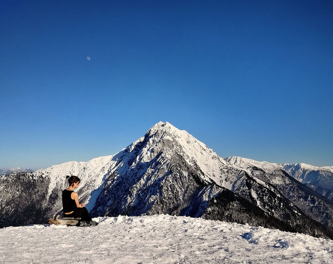 Man sitting on snowcapped mountain against clear blue sky