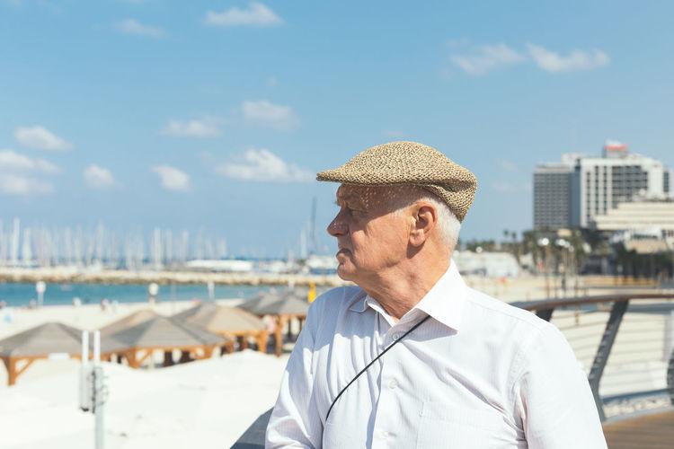 Portrait of man wearing hat against sea against sky
