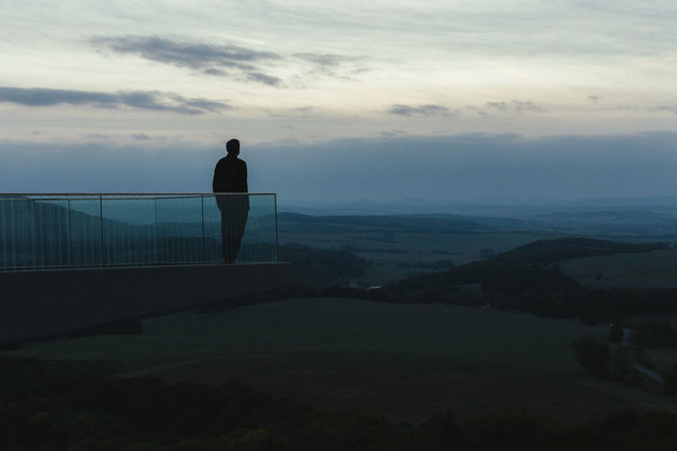 Silhouette man standing on observation point against sky during sunrise