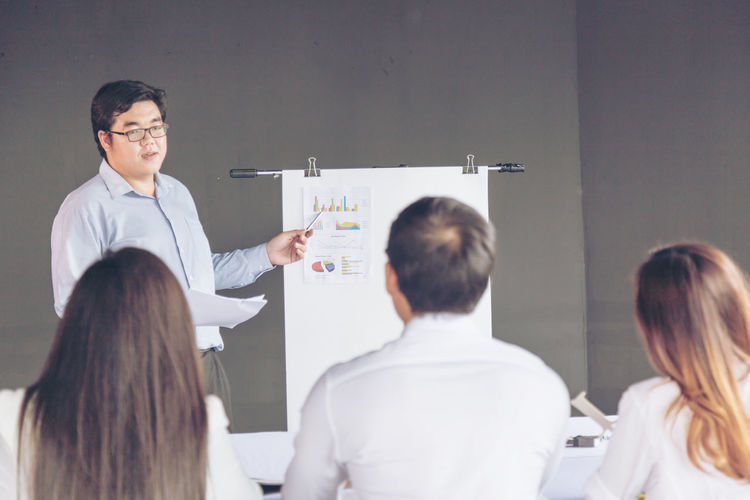 Businessman Discussing With Colleagues Over Flipchart At Office