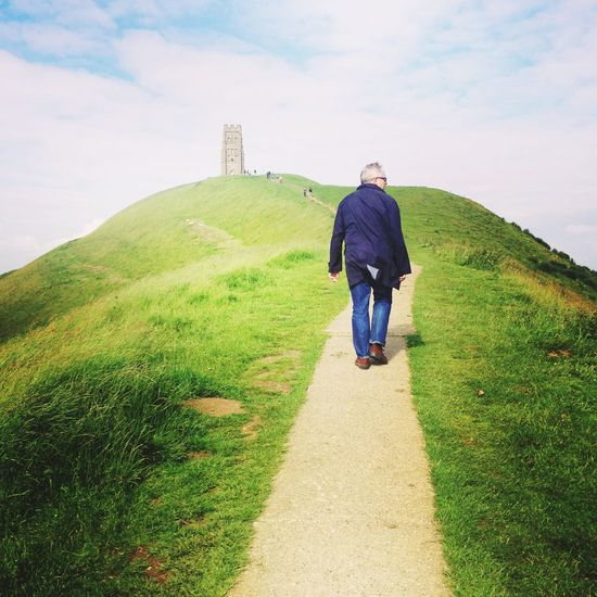 Rear View Full Length Real People Lifestyles Walking Leisure Activity One Person Outdoors The Way Forward Day Nature Sky Grass Scenics Landscape Beauty In Nature Glastonbury Tor TCPM Second Acts