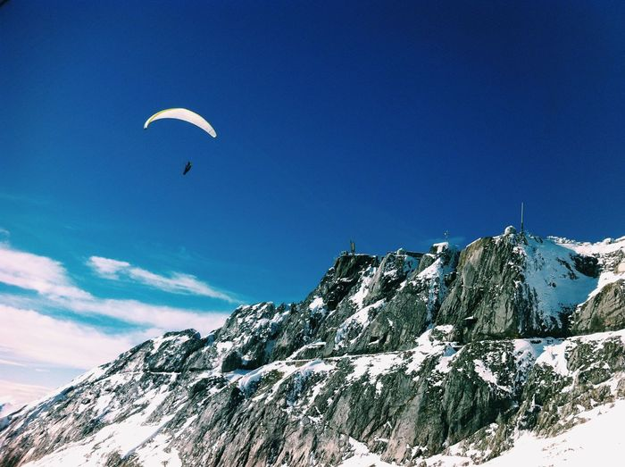 Person parasailing over snowcapped mountain