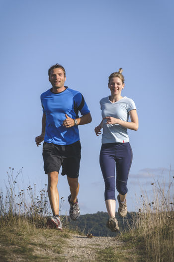 Personal Training Personal Training Running Woman Clear Sky Couple - Relationship Fitness Fitness Training Front View Full Length Jogging Leisure Activity Lifestyles Men Nature Outdoors People Personal Trainer Real People Sport Sports Clothing Together Togetherness Two People Young Adult Young Men