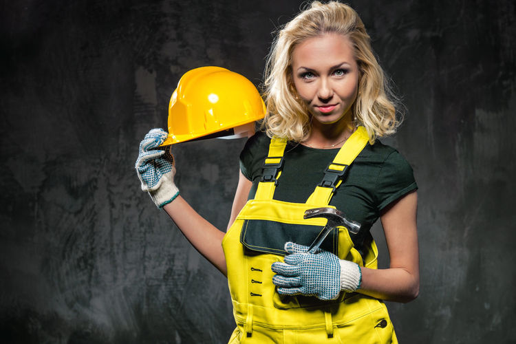 Portrait of confident female worker in bib overalls standing against wall