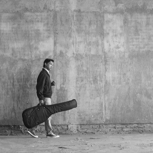 Full side view of a man carrying a guitar on the wall