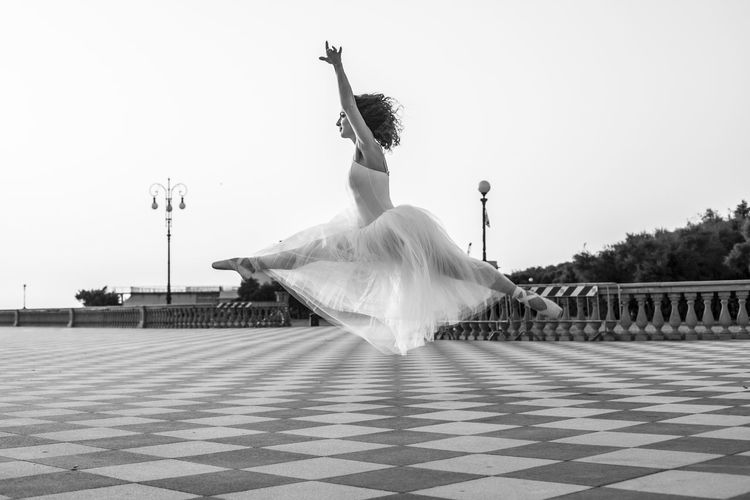 People dancing on tiled floor against clear sky